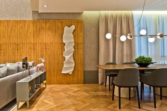 Modern House Karsten - Mariana Paula Souza. O ambiente de 115 m² possui presença marcante de madeira natural. O material aparece tanto no piso tanto nos charmosos painéis de parede que complementam a decoração.