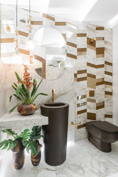 Patricia Zat usou ladrilhos de mármore de diferentes tons para construir um criativo mosaico geométrico na parede do Hall e Lavabo. No piso, a escolha foi um mármore escovado.