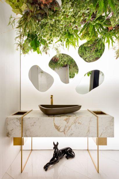 No Toilette Masculino, as profissionais Camila Rocha e Monica Pajewski optaram por espelhos em forma de bolhas para intensificar a leveza do mármore branco. Iluminados por trás, eles complementam a atmosfera cândida do jardim vertical.