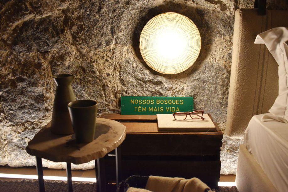 Triplex Arquitetura - Casa Raízes. Com materiais naturais e tons terrosos, a Casa é um local orgânico e vivo, muito essencial. No quarto, uma pequena homenagem à flora brasileira com um trecho do hino repousa ao lado da cama.