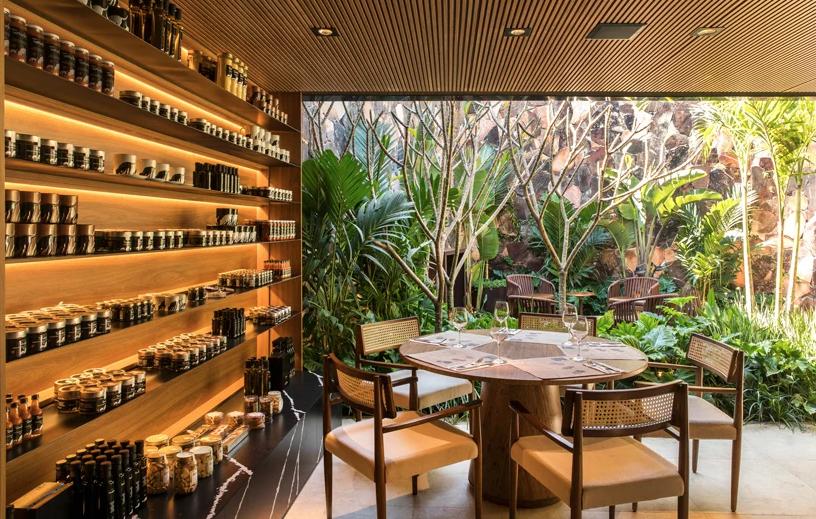 """Tartuferia - mf + arquitetos.<span style=""""font-weight:400;"""">Mariana e Felipe Oliveira apostaram numa estante para abrigar e expor temperos, que ainda recebe luz natural direto do verde ao lado.</span>"""