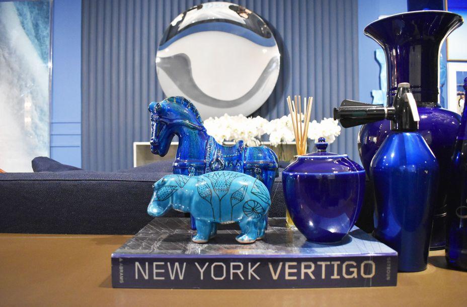 """<span style=""""font-weight:400;"""">A escolha de Bruno Carvalho, no espaço Hall da Biblioteca, ficou nos dois animais de fazenda na mesa atrás do sofá, em tons de azul, assim como todo o resto do ambiente.</span>"""