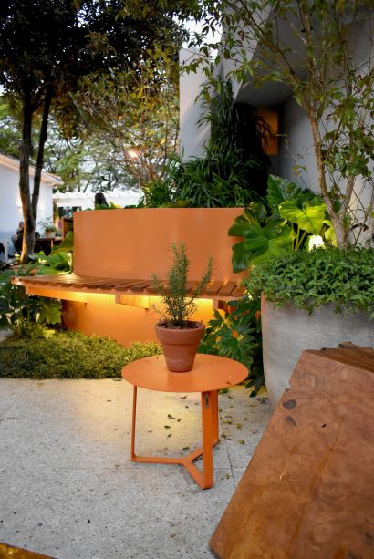 <span>Coliving - Clariça Lima. Os bancos em aço corten trazem um contraste de cor bem-vindo, em meio à vegetação que abraça e convida a uma pausa.O alecrim foi inserido em um vaso em uma das mesas de centro.</span>
