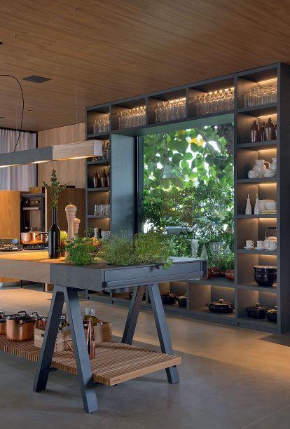 <span>Casa Terra - Paola Ribeiro. A bancada mista de pedra e madeira abriga uma pequena horta com temperos para cozinhar.</span>