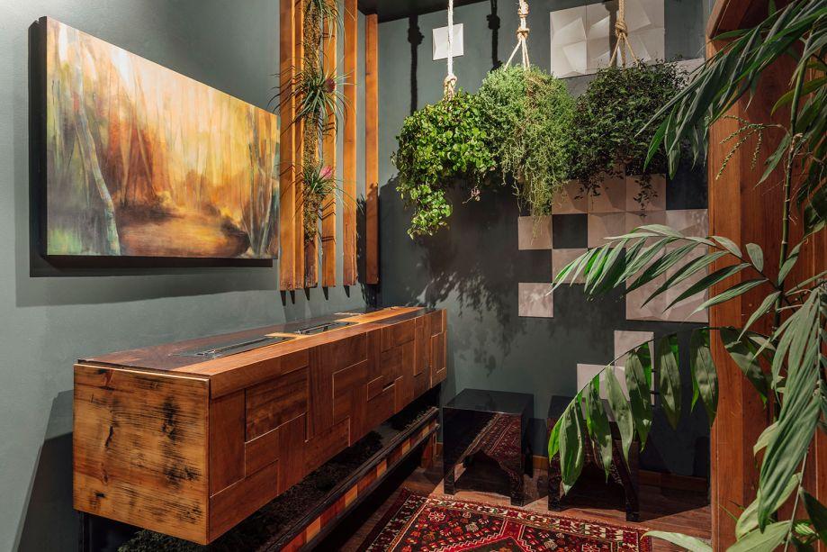 Espaço Life - Jotha Designer. O espaço junto à escada inclui um lavabo e está na transição entre ambientes. Ele promove um encontro com a arte contemporânea e fortalece o conceito Casa Viva, seja no jardim suspenso ou no aparador em madeira de demolição, criado por Jotha.
