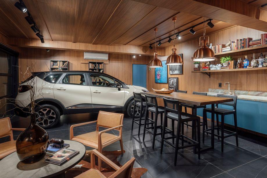 Garagem Renault Home SPA - Luiz Sentinger. Estes 60 m² combinam espaço gourmet com bar e sala de banho com SPA. Teto e paredes ganham painéis de MDF no padrão freijó, da Duratex. Já a bancada é de madeira maciça, acompanhada pelas banquetas Liv, de Luan Del Savio. Ele também assina as cadeiras em jequitibá e couro caramelo ao redor da mesa de centro Concrete, de Diogo Tomazzi.