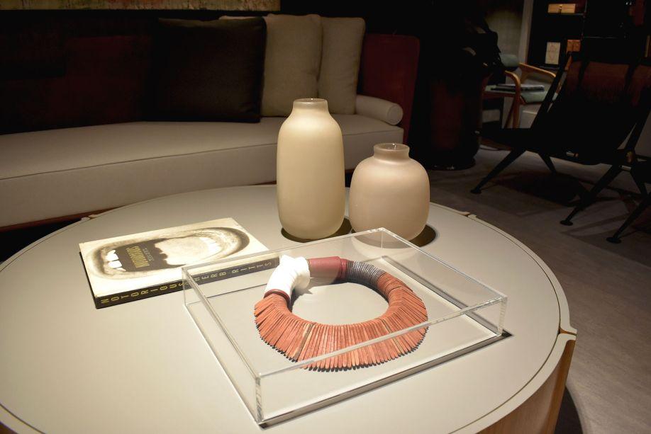 """<span style=""""font-weight:400;"""">Na Casa Essencial, de Gustavo Martins, os objetos são o destaque: paredes e objetos neutros favorecem o destaque de vasos, plantas e, principalmente, do colar indígena, que está bem no centro da sala.</span>"""