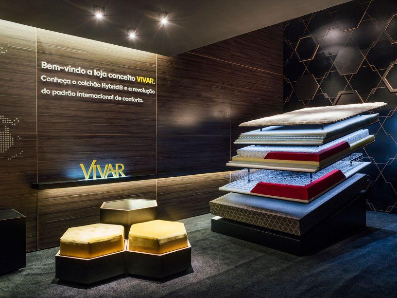 Loja Conceito Vivar - Criaforma Arquitetura. Com um quê minimalista e industrial, a proposta desconstrói os elementos que compõem os colchões, principais produtos da loja. As molas, por exemplo, compõem uma das divisórias do espaço. Além de tecnológico, o clima é intimista, com painéis em MDF escuro nas paredes e a luz cênica pontual.