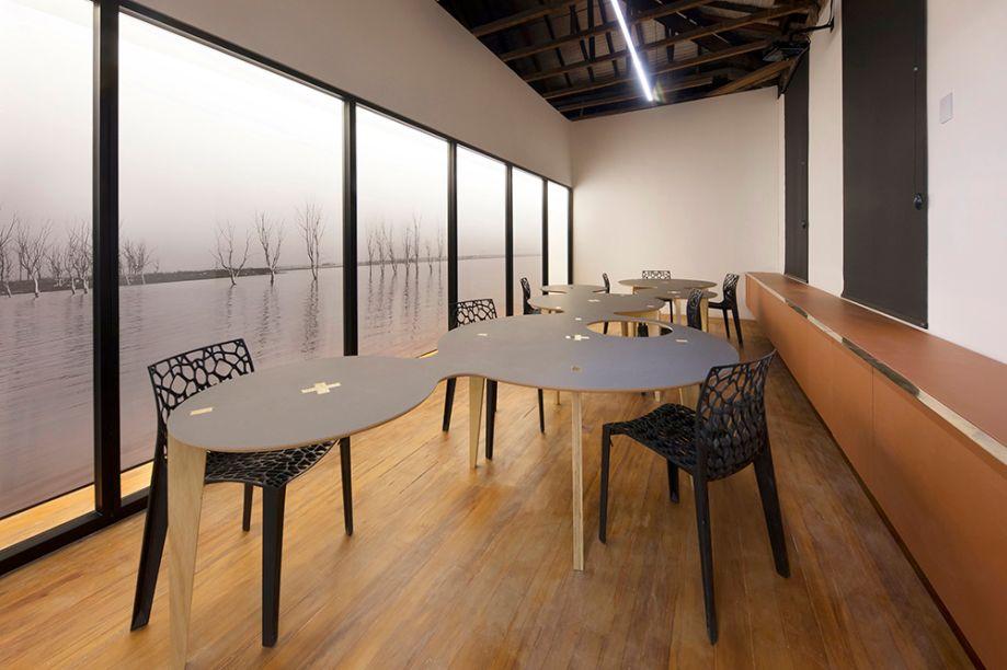 Estufa Criativa UniBH - Dois Arquitetura (José Ricardo Fois e Renata Rocha) e Rafael Prates Yanni. A mesa em pinus, MDF e latão é um exercício de fabricação digital feito pelos arquitetos e se molda a várias funções, neste misto de coworking, home office, biblioteca, estúdio, laboratório. O aparador Ceramik acentua a linearidade e a simplicidade do espaço, sugerindo atravessar a parede. Do lado oposto, painel com a obra Epecuén, do fotógrafo Daniel Mansur.
