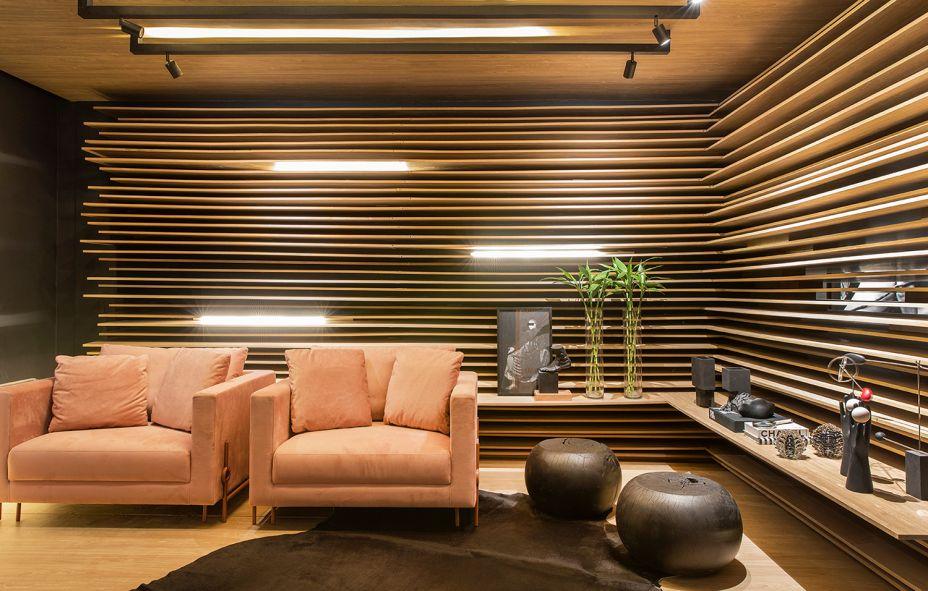 Lounge/Bilheteria Arauco - Arqsign. Depois de atravessar um túnel verde, o visitante encontra este lounge onde a matéria-prima predominante são as lâminas de MDF. Elas são utilizadas de forma inesperada nas paredes, acompanhando o tom amadeirado do teto e do piso. Nas poltronas, o rosé traz suavidade.