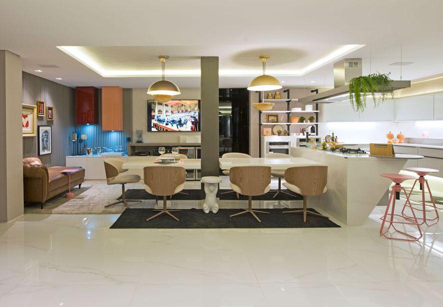 Cozinha Lounge Jardim - Maria José Lopes. A árvore do lado externo é a atração principal do ambiente. Com o uso mínimo de paredes e barreiras, cozinha, lounge e jardim formam uma harmonia estampada à frende da cor branco, no plano de fundo. A versatilidade e infinitas possibilidades de uso marcam o ambiente, carregado de móveis modernos.