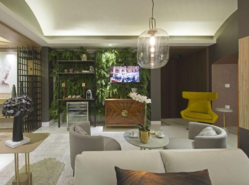 Saleta Verde - Maria José Lopes. Um mix de textura, cores e formas, presente nos móveis, paredes e teto, trazem a leveza para o ambiente. O papel de parede listrado está em harmonia com o telhado de vidro, que possibilita visualizar o jardim como um todo. As poltronas individuais trazem modernidade ao espaço.