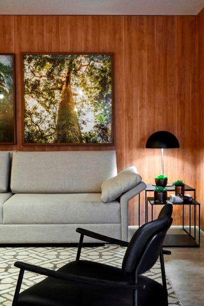 Lounge Resort - Gui Rodrigues. Nesse ambiente, as árvores estão presentes em fotografias as quais, junto de plantas, preenchem a estante que divide o ambiente.