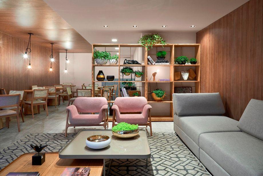 Lounge Resort – Gui Rodrigues. A mistura de materiais com apelo natural é o destaque nestes 68 m². Teto e paredes recebem placas de MDF. Já o piso traz um laminado no tom de concreto. Plantas e objetos se inserem na estante que divide espaços, pontuados por móveis modernos e lâmpadas de LED. As poltronas rosa millennial quebram a formalidade.