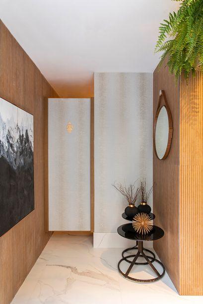 Banheiro dos Encontros - Carol Azevedo. Para criar um espaço agradável de encontros e bate-papo, foram adotados revestimentos de madeira nas paredes e um toque de verde natural para refrescar. Como em uma sala de estar, complementos, obras de arte e o papel de parede conquistam o espaço de forma pontual.