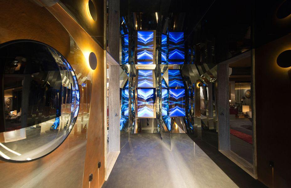 Galeria Viva - Racine Mourão. A proposta é transformar os visitantes nos personagens principais do ambiente. Composto por um corredor de espelhos, que permite uma visão completa de si mesmo a partir de diferentes ângulos, e também do teto, o arquiteto convida o espectador a uma reflexão. A iluminação indireta destaca ainda mais os espelhos.