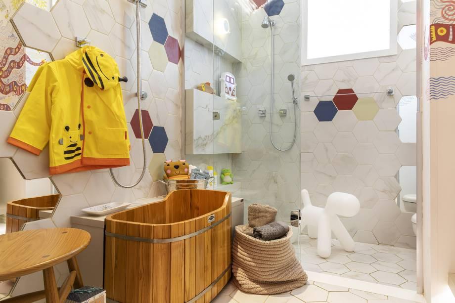 Banheiro da Criança - Lucéia Ambrózio Inspirada no método Montessoriano, a arquiteta projetou um local que pudesse contribuir de forma positiva com o desenvolvimento e independência da criança.A cuba, envolvida pelo lavatório de MDF, faz a vez de um degrau que dá acesso à torneira.Os nichos de MDF coloridos auxiliam a cuba, contendo objetos para higiene pessoal e brinquedos lúdicos que ficam à vista e à mão para que possam ser utilizados pelos pequenos, sem que eles precisem, para isso, de um adulto.Junto ao Ofurô há uma barra deslizante com ducha manual onde a criança pode operar o jato de água de forma prazerosa e funcional. Sobre o apoio de madeira que serpenteia o Ofurô, encontram-se livros de banho e objetos para higiene pessoal podem ser facilmente encontrados.