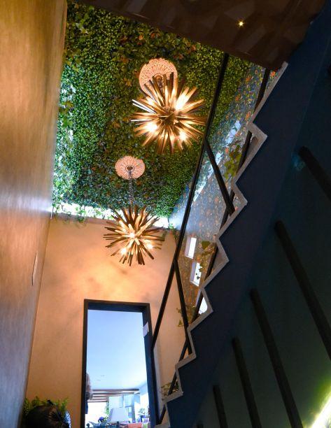Escalinata Principal - Luis Escobar e Natalia Aguirre.A escada é o elo vital da casa e ganha a importância que merece, transformada com uma variedade de texturas e cores que evocam a natureza. Várias referências se encontram, como o exuberante jardim que dá vida ao teto, onde também habitam dois pendentes glamourosos.