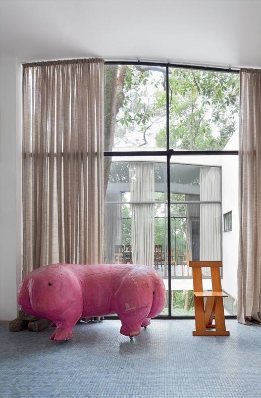 Polochon original na Casa de Vidro. Janela ao fundo e uma cadeira de madeira ao ladoira