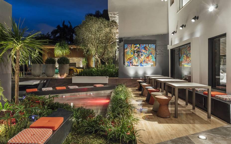 O arquiteto Lucas Prates, da Lupa Multistudio, apresenta o ambiente Shuffle - O Pátio do Músico. Aqui, o paisagismo contrasta com as cores escolhidas nos móveis e com o quadro na parede principal. Os bancos são aquecidos através de tecnologia de placas solares.