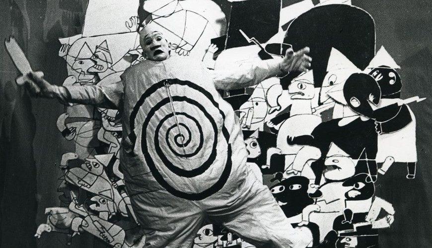 Cena da peça Ubu Rei. Homem com maquiagem cênica veste um macacão com enchimento com uma espiral estampada