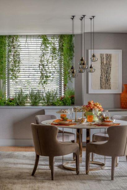 Living da Casa Viva - Ana Lúcia Jucá. Estilos clássicos e contemporâneos se misturam e usam a cor cinza como base. Na janela, duas soluções são apresentadas: uma horta para a cozinha e um jardim suspenso na sala de estar, que traz natureza e praticidade para a concepção.