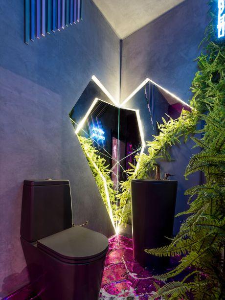 O Ateliê da Alma - Laura Giassi Morastoni e Bianca Steinmetz de Souza. O geometrismo do espaço principal se repete em seu lavabo. Na parede, o recorte revestido em espelho é sublinhado pela iluminação e instiga o olhar. A parede com aparência de concreto e as louças em preto fosco se contrapõem ao verde que conquista seu lugar.