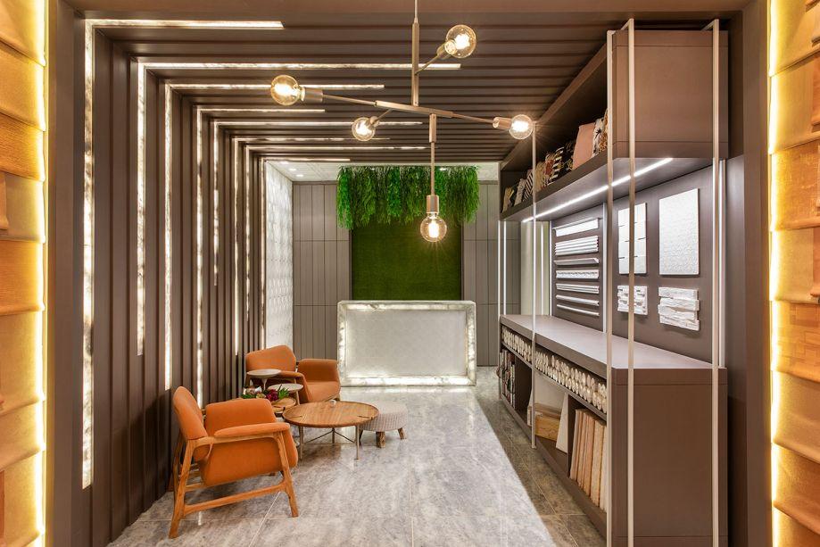 Wallpaper Store - Amanda Lyra Falquetto, Leticia Giuberti e Natusa Croce. Neste ambiente, o mesmo material da parede sobe para o teto e ganha um charme: frestas iluminadas de mármore translúcido, trazendo leveza e elegância ao projeto.
