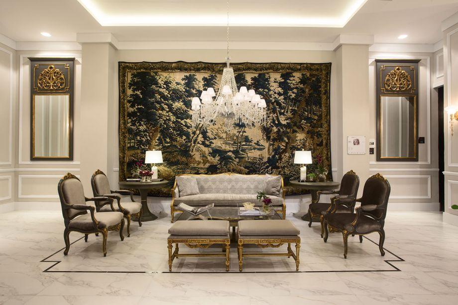 Bien Venue - Milena Niemeyer. Boas-vindas no melhor estilo clássico marcam o foyer de entrada. Uma grande sala de estar, majoritariamente branca, cria um ambiente sofisticado e elegante, destacando as peças de mobiliário e decoração.