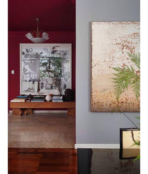 Em planos diferentes, a parede cinza recebe a tela de Clayton Assaf e a parede vermelha, a obra de Marco Magalhães.