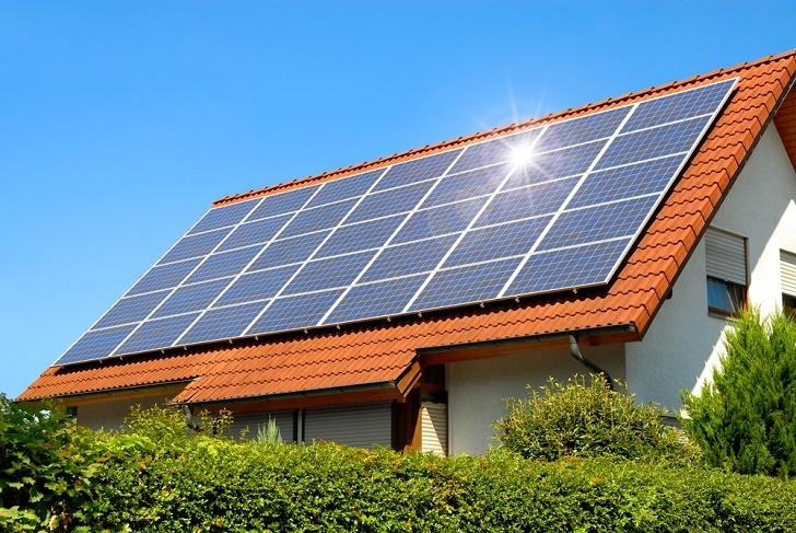 Casa com cobertura de telhas. Sobre as telhas, placas solares