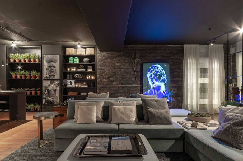 CASACOR São Paulo 2018:<span>Lounge Sensações™ - Gustavo Paschoalim. A cozinha gourmet é integrada ao amplo living, totalizando 92 m². Com a pegada dos lofts americanos, utiliza piso de demolição de bambu, iluminação em trilhos aparentes e tijolos ingleses nas paredes. A decoração é exposta nas estantes e inclui objetos dos séculos 18 e 19. O estilo prático se confirma na mesa extensa e multifuncional. Para suavizar, estofados azuis.</span>