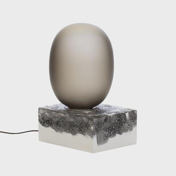 """A marca alemã Pulpo adiciona diversas luminários ao seu portfólio com a coleção 'Light Now, Vol. I'. Colaborando com Sebastian Herkner, Ferréol Babin, os trabalhos expressam a inovação da marca com materiais. A epça escultural da foto é feita de cerâmica e lava, como seu título """"Magma"""" sugere. Esta base orgânica suporta o globo de vidro em um contraste intrigante de materiais."""