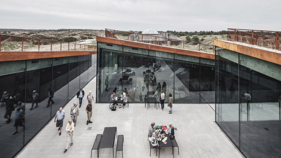 <strong>Museu Tirpitz</strong>; Blåvand, Dinamarca, por Bjarke Ingels Group (BIG). Um santuário situado em um local de história de guerra dramática na costa oeste da Dinamarca, este museu transformou um bunker alemão nunca concluído, em um complexo cultural inovador. Antagônico aos dias sombrios da ocupação da Segunda Guerra Mundial e ao peso do bunker de cimento, a delicada intervenção dos arquitetos adiciona uma praça pública central cercada por espaços cheios de luz embutidos na paisagem.
