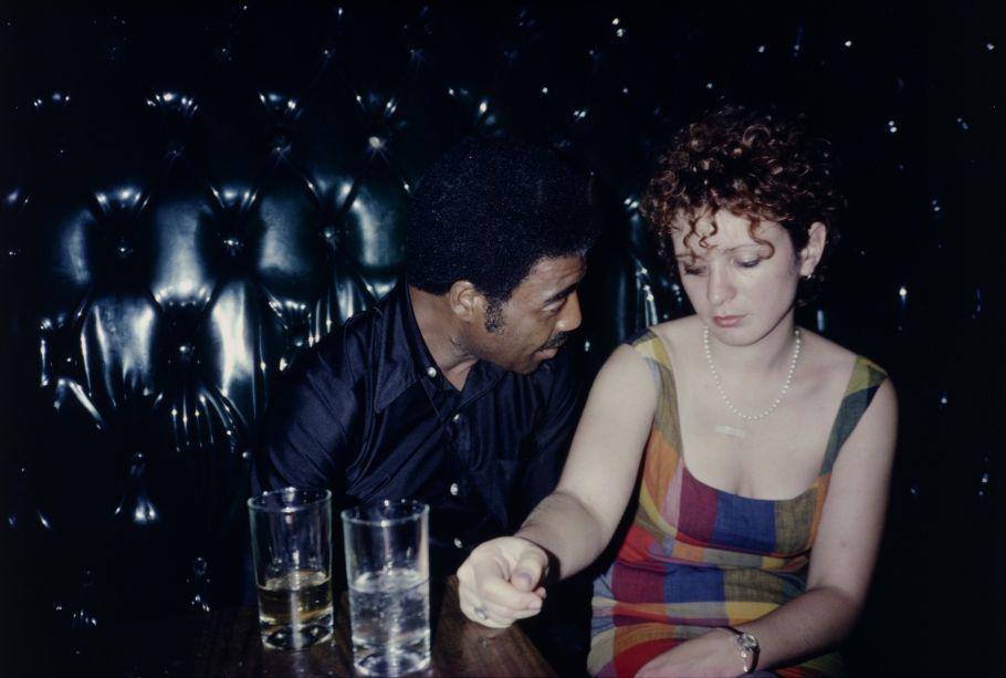Nan Goldin (Washington, D.C., 1953) é uma fotógrafa americana, que cresceu em uma família judia de classe média alta em Boston, Massachusetts. Em 1968, um professor da escola em que estudava, a Satya Community School, introduziu-a à câmera fotográfica. Sua primeira mostra solo, realizada em Boston em 1973, foi baseada em suas jornadas fotográficas através das comunidades gays e transexuais da cidade. Goldin graduou-se na School of the Museum of Fine Arts, Boston/Tufts University em 1977/1978, onde trabalhou na maioria com impressões através do processo de Cibachrome. Depois de se formar, Goldin mudou-se para Nova Iorque e começou então a documentar o cenário new-wave pós-punk, simultaneamente à subcultura gay no final da década de 1970 e começo da década de 1980.