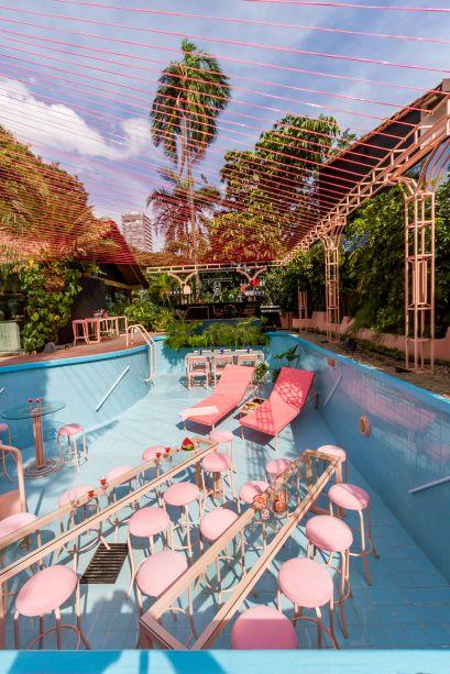 Bar Orgánico - David Arias F. e José Jordan. O bar ocupa a piscina, cuja forma foi mantida e ganhou uma cobertura de cordas vermelhas, que combina leveza e movimento. O jardim foi integrado ao conjunto e, para isso, apostaram em elementos clássicos e coloniais da arquitetura e da cultura de Santa Cruz. Eles conversam com os rosas e metalizados, com o clima de uma glamourosa pool party.