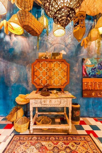 """Mercado CASACOR - Carlos X. Araùz e Fernando Justiniano. Como nos vibrantes bazares turcos ou mercados marroquinos, este espaço maximalista guarda diferentes combinações de cores e detalhes. Muitos materiais utilizados são reciclados e compõem com talhas de madeira, pedras, mármore, tecidos e fios de cobre.""""É como um misterioso bazar, onde é possível encontrar de tudo, desde bugigangas até objetos de design como as famosas vacas decorativas """", disseram."""