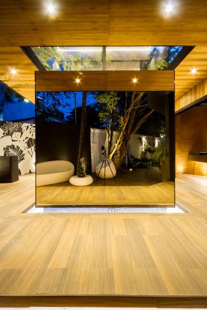 Baño: Reflex Box - Hebert Vargas e Nataly Dorado. CASACOR Bolívia 2019. Ao centro do banheiro, surge um espelho de água. Sobre ele, foi posicionado um cubo espelhado que dá a sensação de estar flutuando - a caixa de reflexos do projeto. No alto, a abertura revela a vegetação que envolve o espaço.