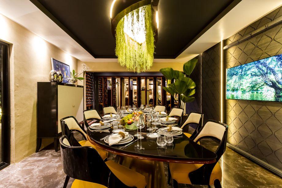 Comedor Principal - Rudy Rivero e Sofía Suárez. O formato da mesa de jantar simboliza uma folha e, nela, madeira, metal e vidro se combinam. As cadeiras são luxuosas, assim como a tapeçaria em tons de branco e laranja. A cor preta confere a formalidade pretendida pela dupla, trazendo sofisticação.