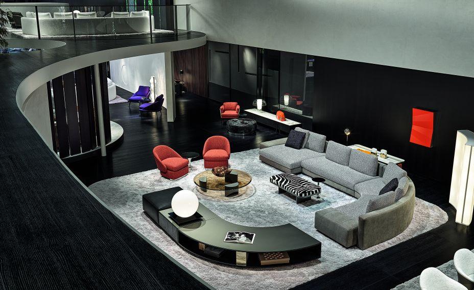 Além de confortáveis e espaçosos, os sofás também ajudam a dar forma à sala, criando um movimento que delimita a área de convivência. A mesa lateral também segue a mesma curvatura do sofá, assim estabelecendo uma dinâmica configuração em 'U'.