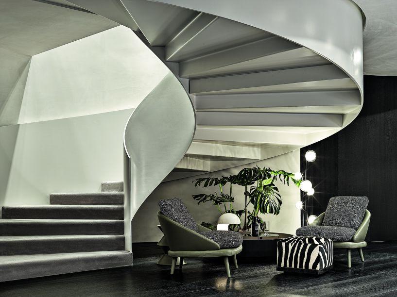 As duas escadas em espiral, uma em cada extremidade do espaço, enriquecem o ambiente como um elemento arquitetônico arrebatador, que também seguem o padrão redondo da exposição.