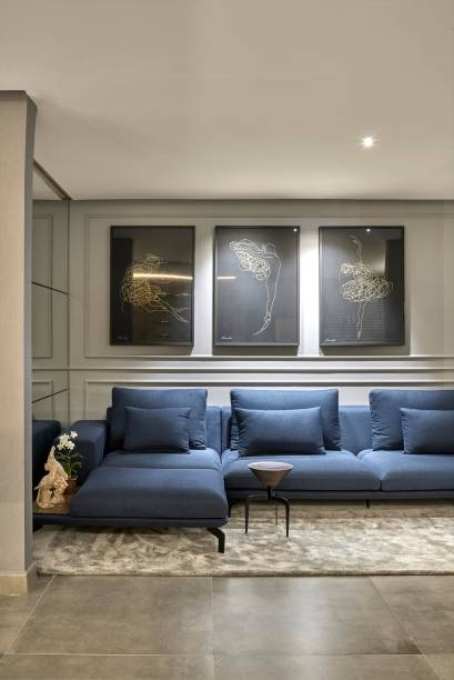 Sala de Jantar – Mayra Oliveira. As paredes com boiseries trazem um toque clássico ao espaço contemporâneo. Neste detalhe, todas as peças foram assinadas por designers e artistas goianos. As telas são da artista Heloisa Lobo.