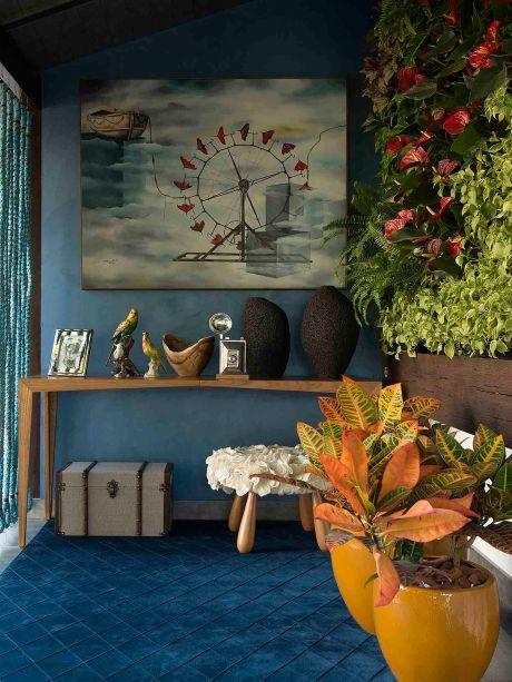 Varanda do Lago - Larissa Palma Dias. Com jardim vertical, lareira e balanço, o ambiente de 12 m² é totalmente aproveitado para valorizar a relação com a natureza. O azul profundo faz um contraste com os tons quentes dos crótons. No mobiliário, peças do designer Aristeu Pires, junto com obras de arte e objetos de decoração exclusivos.