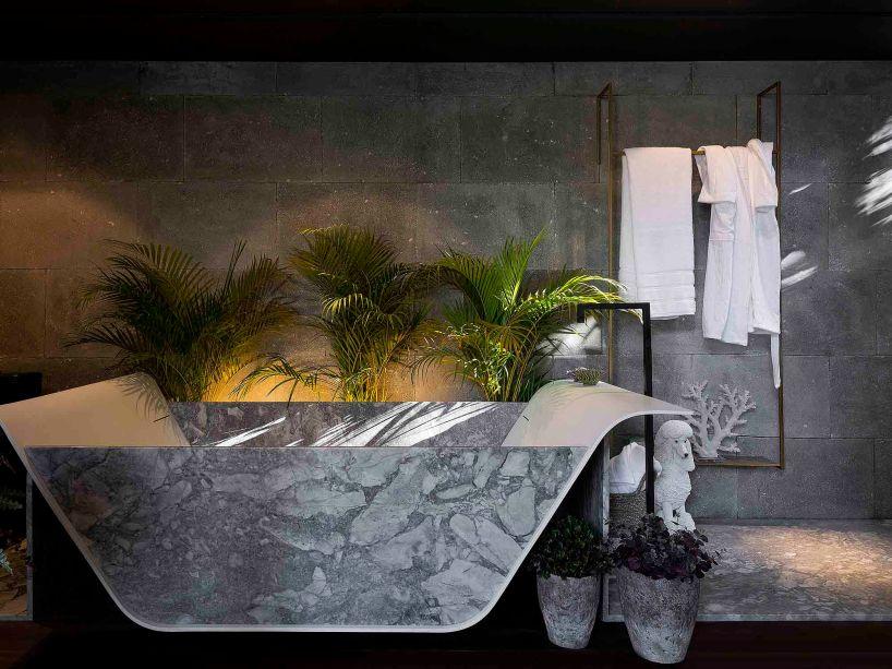 Refúgio da Artista - D'Fatto Arquitetos Associados. No loft em meio a natureza, cada elemento traz algo de surpreendente e conceitual. Um deles é a sala de banho que explora o mármore e as pedras. Seria uma instalação monocromática, não fossem as plantas e a iluminação quente posicionada atrás da banheira.