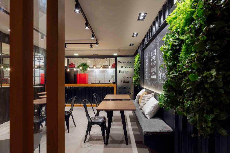 Pane Pizza - Luciana Pestana.O estilo industrial prevalece na pizzaria, de apenas 32 m². Nos revestimentos foram utilizados metais, madeira e tijolos com malha de ferro sobreposta, amenizados pelos quadros verdes e a iluminação direcionada em tons quentes.