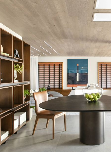 C4 Arquitetos - Living Perene. A madeira assume papel de destaque no teto, recortado por claraboias. Elas aproveitam a luz natural. assim como as generosas janelas de freijó. A mesa tem design de Arthur Casas.