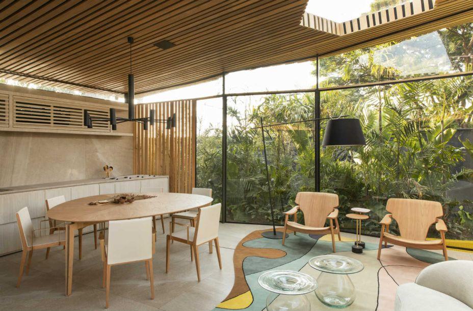 Mariana Orsi - Loft DECA. Os 56 m² se expandem e adquirem a dimensão do jardim que adentra o espaço integrado. Painéis de vidro são responsáveis pelo fechamento, enquanto o teto, recortado por algumas aberturas, é revestido de Tauari maciço. Um material que remete a uma casa de palafitas. As poltronas Diz são de Sergio Rodrigues.