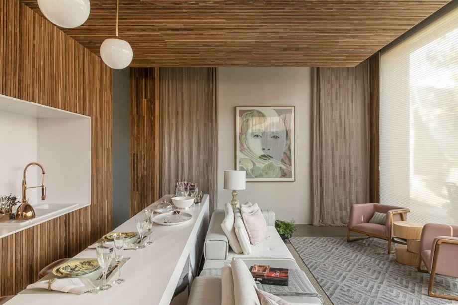 Simone Pedreschi - Loft Essência Feminina. A sala e a cozinha estão sob o mesmo teto de madeira ripada, que desce pela parede. A área funcional com a pia foi encaixada no nicho, em um exemplo da linguagem minimalista que define o projeto.