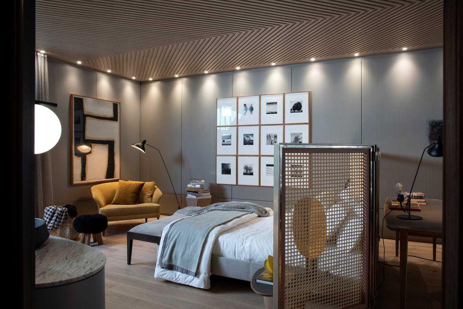 Denise Barretto - Atelier de Morar. O ambiente de 130 m² foi delimitado de várias maneiras, sem perder a fluidez. Uma das ideias foi utilizar o biombo de cedro e palhinha, que funciona como cabeceira e divide o quarto do escritório.