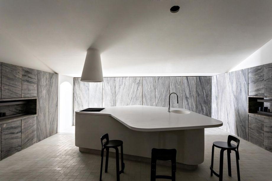 Cucina Pietra - Felipe Hess. Minimalista e elegante, a cozinha é limpa de interferências visuais, com uma ilha central e uma coifa que parece de desdobrar do teto. Ali, destacam-se, ainda, as banquetas desenhadas por Alvar Aalto.
